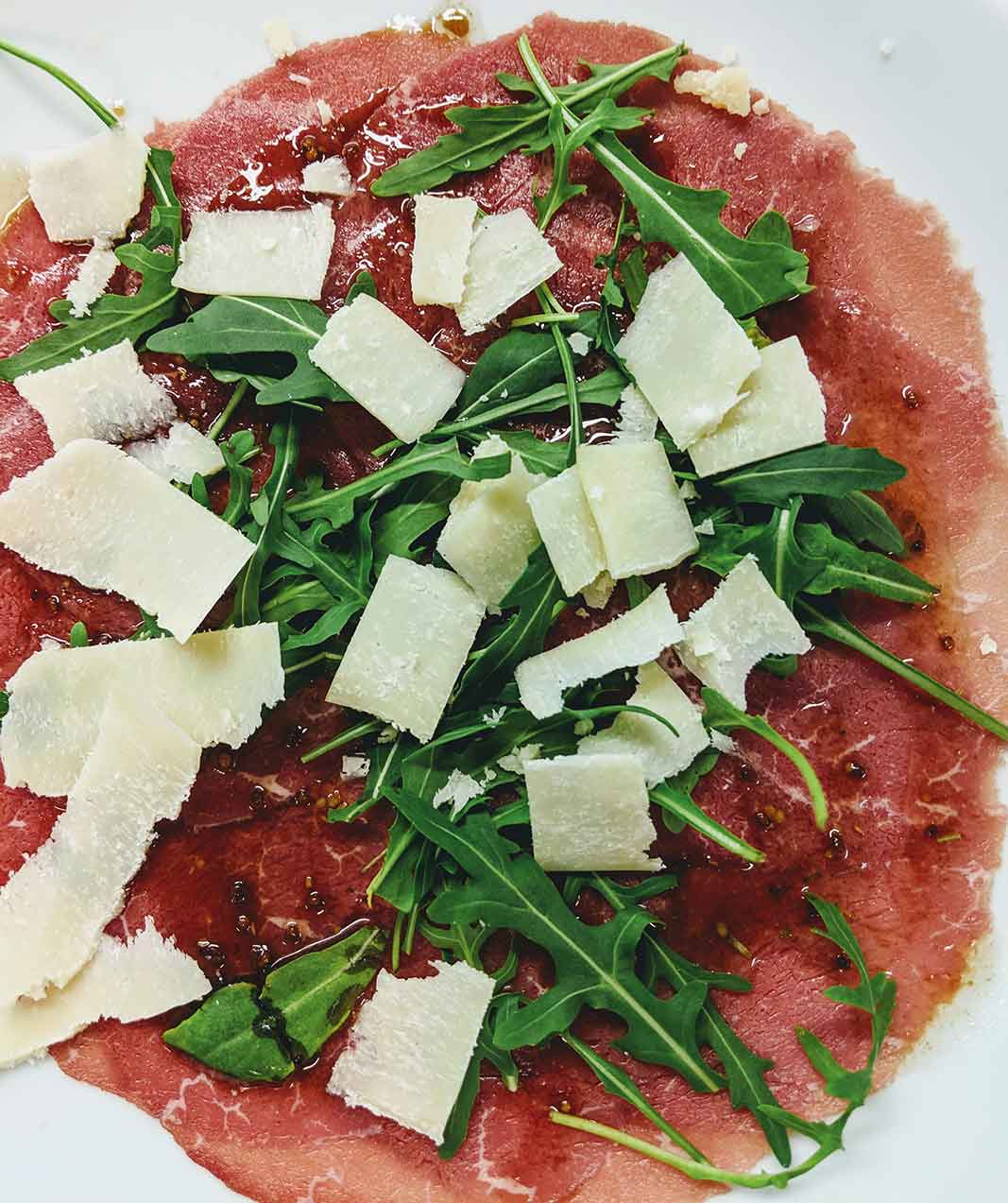 Beef carpaccio with Parmesan cheese, rocket salad and mustard vinaigrette